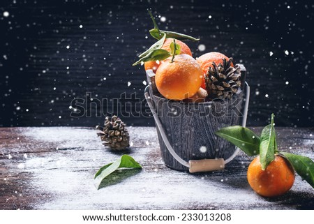 Wooden bucket with tangerines over wooden background with snow and cone.