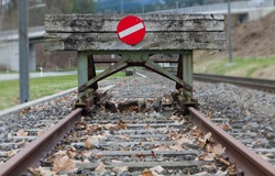 wooden buffer stop with red stop sign ending rail tracks concept for limit, limitation restriction boundary, prohibited, end , border