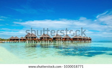 Wooden bungalow on the background of azure water and blue sky, Maldives #1030018771