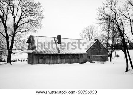 Wooden cabin in a snow filled field surrounded by trees