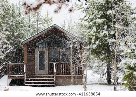 Wooden cabin in snow storm with trees