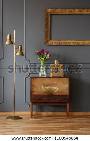 Wooden cabinet decorated with flowers and vase next to a lamp in a hallway interior with wall molding a golden frame #1100648864