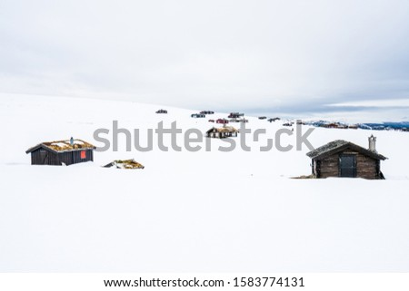 Wooden cabins outdoors in beautiful snow covered mountains and foggy scenery in the background. Architecture and season concept. From Rondane national park in Norway. #1583774131