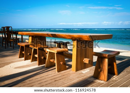 Wooden cafe table and chairs on a tropical beach on a tropical beach with blue sea on background