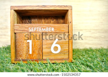 Wooden calendar on September 16 on a green grass background.World ozone day. #1502534357