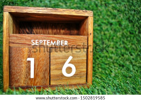 Wooden calendar on September 16 on a green grass background.World ozone day. #1502819585