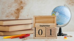 Wooden calendar September 1 on a stack of books, globe. Concept for Knowledge Day, beginning of school year. Copy space.