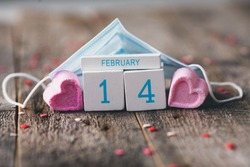 Wooden calendar with date of February 14 on wooden background. A house made of a medical mask and cubes. Valentine  Day during a pandemic COVID-19 .