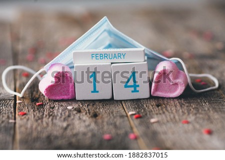 Photo of  Wooden calendar with date of February 14 on wooden background. A house made of a medical mask and cubes. Valentine  Day during a pandemic COVID-19 .