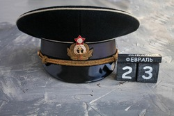 Wooden calendar with the date of February 23, and  headgear officer of the Navy of the USSR and Russia Defender of the Fatherland Day. Men day in Russia. Text in Russian on February 23.