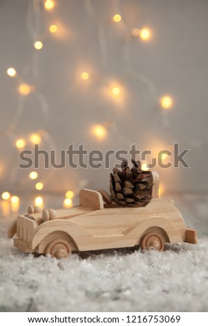 wooden car with pine cone on a wooden gray and snow background and lights from the garland. Christmas card #1216753069