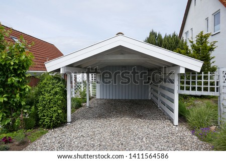 Wooden carport with pitched roof, white with open driveway on pebble floor next to a house. Germany, Europe  #1411564586