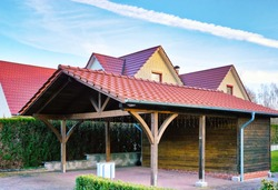 Wooden carport with red brick roof on a new house.
