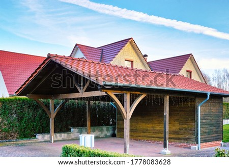 Wooden carport with red brick roof on a new house. Foto stock ©