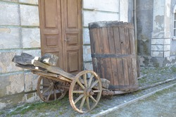 Wooden cart and wooden barrel on the background of the old facade of the house. The facade of an old house with wooden brown doors. Beautiful old composition on the background of the facade of the hou