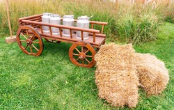 Wooden cart in vintage style, loaded with metal milk canisters. Sheaves of hay lie next to the cart. Farm equipment as elements of landscape design.