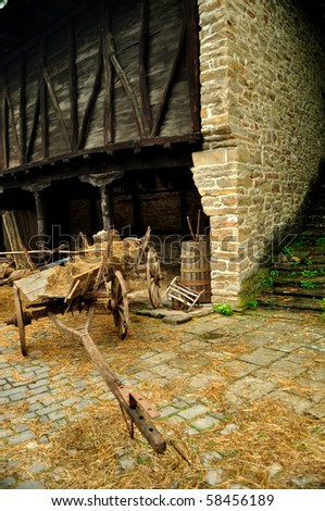 wooden cart with dried hay in front of an old barn