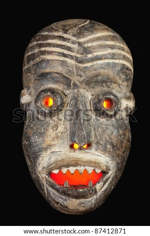 Wooden carved African tribal mask, dark wood with painted face. Isolated on black  background. Congo, Africa