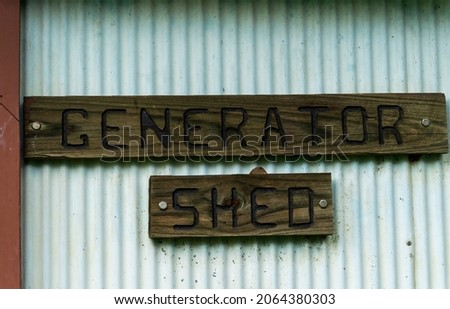 Wooden carved generator shed signage on corrugated iron wall