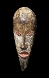 Wooden carved voodoo tiki mask isolated on a pitch black background.