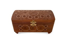 Wooden casket inlaid with beads and decorated with patterns on white background. Jewelry box made of wood with additional workmanship and decorated. Wooden closed carved casket handmade.