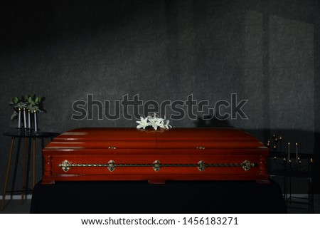 Wooden casket with white lilies and burning candles in funeral home Сток-фото ©