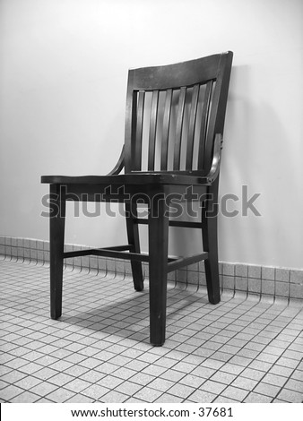 wooden chair against a wall on tiled floor black and white shot from a low down angle stock. Black Bedroom Furniture Sets. Home Design Ideas