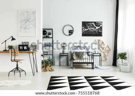 Wooden chair at desk with laptop in workspace in monochromatic boy's bedroom with carpet, round clock and plants #755518768
