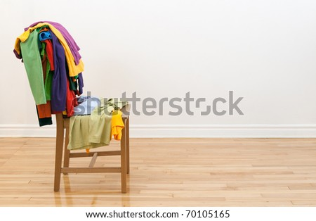 Wooden chair in a room, with lots of colorful messy clothes on it.