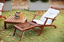 Wooden chair in autumn garden. Vintage radio on table. Wooden deckchair on green summer lawn on picnic. Lounge sunbed. Wooden garden furniture on grass lawn outdoor for relax. Backyard exterior.