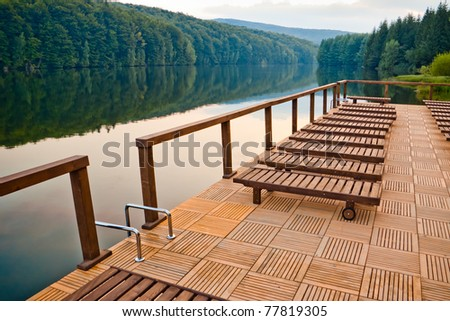 wooden chair on lake dock at sunset