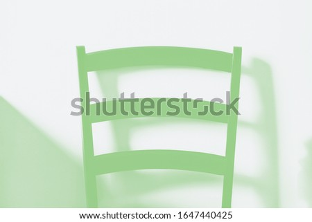 Wooden chair on wall background. The back of the chair, detail. Light and shadows. Minimal style, minimalism, green toned