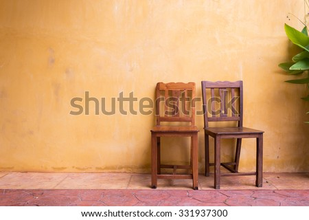 wooden chair seat and orange cement mortar wall background