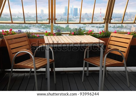 Wooden chairs and table at terrace in empty restaurant; panorama of Moscow