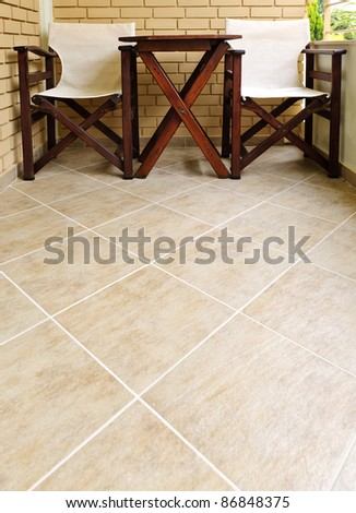 Wooden chairs and table on ceramic tile floor of balcony