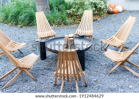 Wooden chairs arranged in a circle. Resting place with fireplace and chairs around. ストックフォト ©