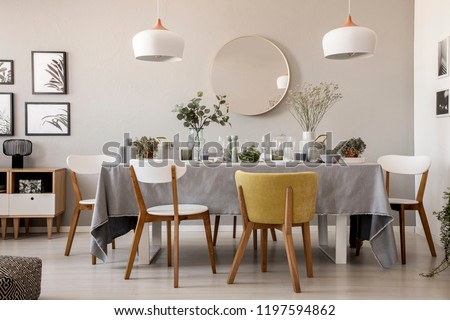 Wooden chairs at table with tableware in dining room interior with lamps and round mirror. Real photo #1197594862