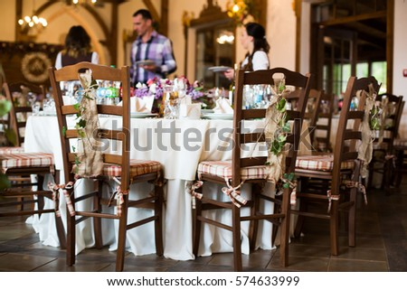 Wooden chairs decorated with greenery stand around white tables prepared for festive dinner