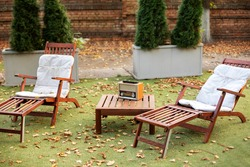 Wooden chairs  in autumn garden. Vintage radio on table. Two deckchairs on green summer lawn on picnic. Lounge sunbed. Wooden garden furniture on grass lawn outdoor for relax. Backyard exterior.