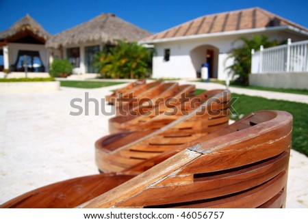 Wooden chairs near swimming pool