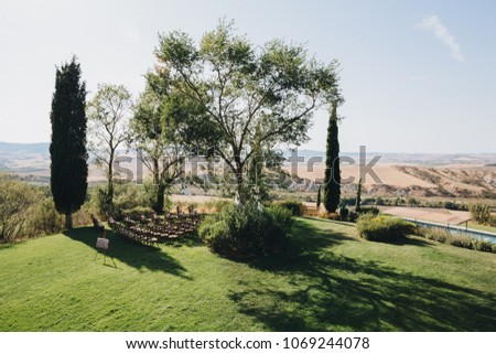 wooden chairs stand on green hill in the wedding ceremony area against the background of Tuscany landscapes