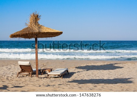 Wooden chairs under umbrella on sand beach
