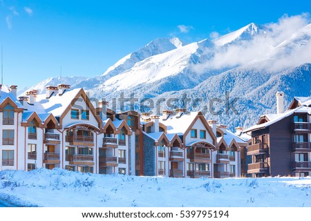 Wooden chalet, houses and snow mountains landscape panorama in bulgarian ski resort Bansko, Bulgaria #539795194