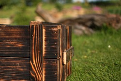 Wooden charred box. Flame tanned wood. Blurred garden background