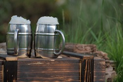 Wooden charred box. Two mugs with beer, white beer foam. Flame tanned wood. Blurred garden background