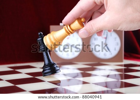 Wooden chess and hand holding the queen