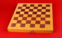 Wooden chess board without pieces on red background