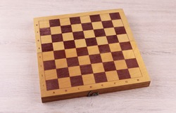 Wooden chess board without pieces on wooden background
