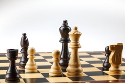 Wooden chess. Chess pieces are located on a chessboard. Black checkmate and win. A chessboard stands on a white background. Closeup