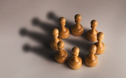 Wooden chess pawn circle with shadow shaped as crown on gray background. Teamwork, group agreement and success concept